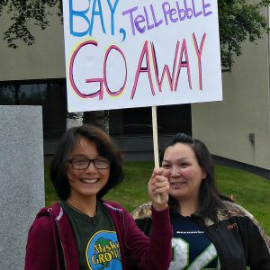 Emily Charles and her aunt hold sign that tells Pebble to go away.