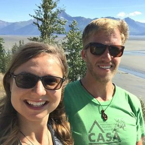 Kat and Dave selfie with blue skies, mudflats and mountains behind them.