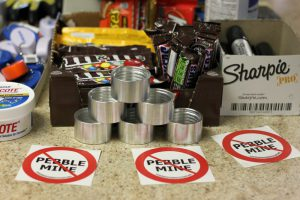 "Photo of ""no Pebble mine"" stickers next to store counter goodies like candy, sharpies, small tins"