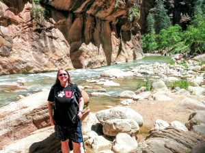 Catherine hiking the Zion Narrows with river and canyon walls in background