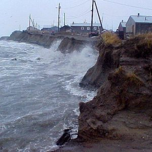 Waves washing against an eroding wall of dirt with a house precariously close to the edge, all due to climate change.