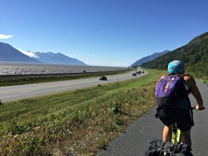 Kat with her backpack riding on the trail beside the Seward Highway.
