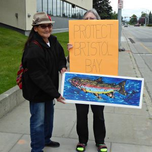 Emily's grandma holds protest signs with a friend during the protest outside the EPA's Anchorage offices.