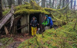 Michelle, Ranger B, and dog Lilly in front of a mossy cabin in Caines Head, Alaska.