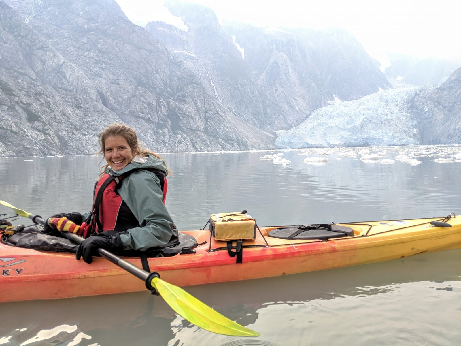 Rachel in a kayak in front of a glacier in Kenai Fjords.