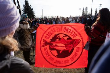 Arctic protectors holding a Defend the Sacred banner. Stop the Arctic Refuge sell-off