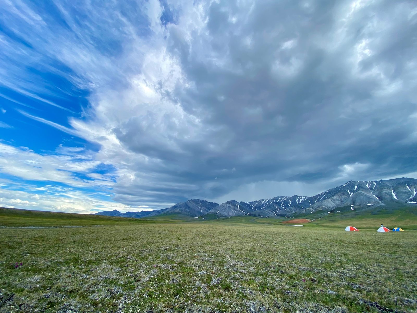 Arctic Refuge awe. A thunderstorm butts against blue sky over the distant mountains and tundra in the foreground, with tents in the distance to the right.