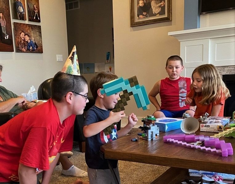 On happiness (and social skills). Kids play with building toys at a coffee table in a room with kid portraits on the walls.